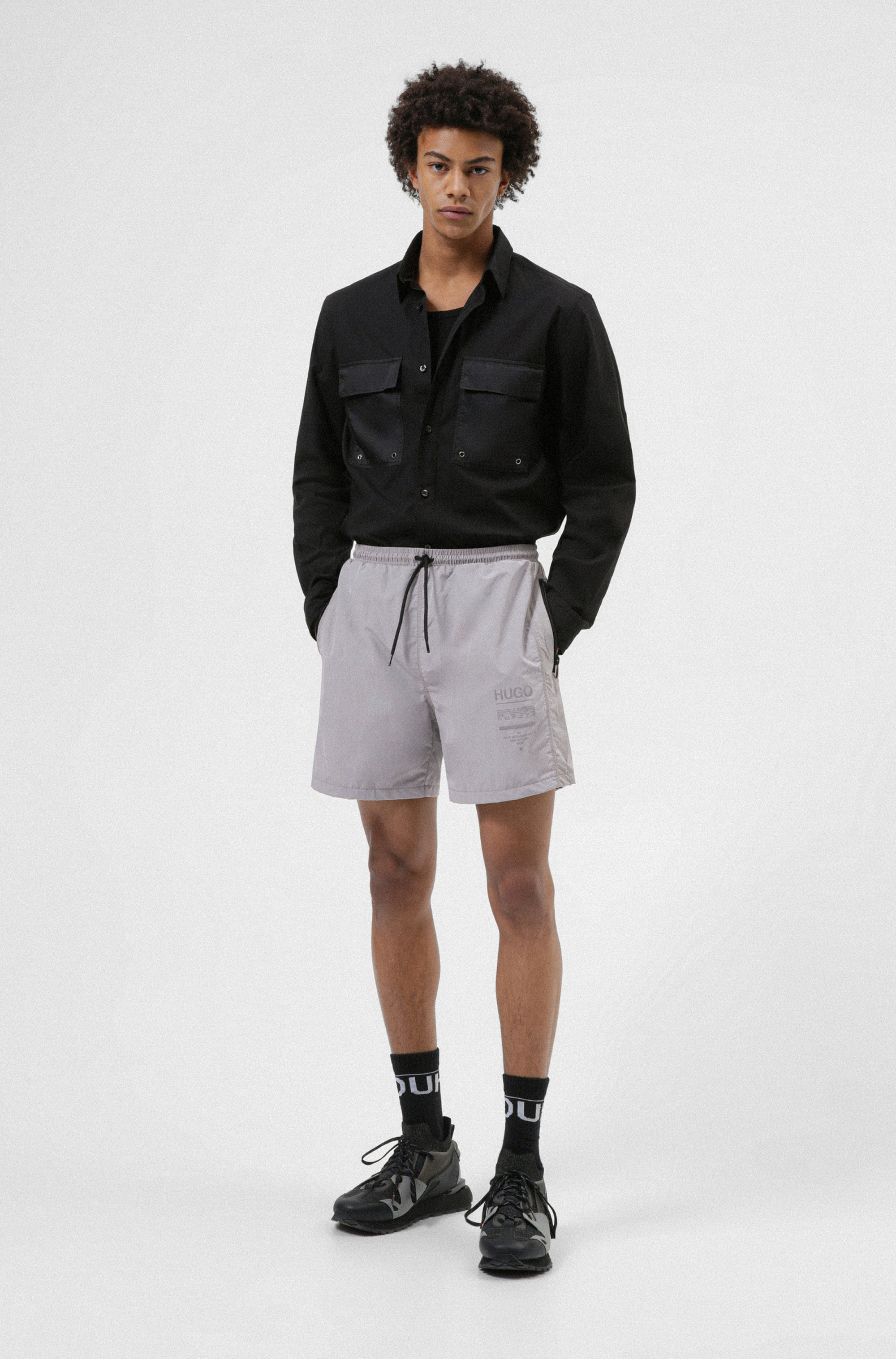 Relaxed-fit shorts with zipped pockets and manifesto print