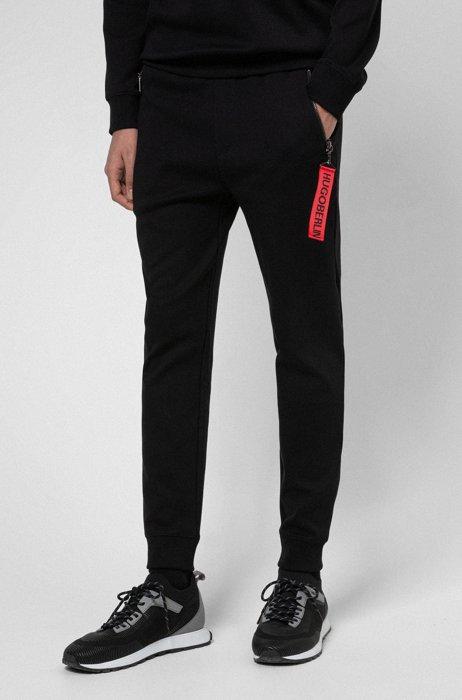 Interlock-cotton tracksuit bottoms with reverse-logo patch, Black