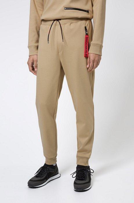 Interlock-cotton tracksuit bottoms with reverse-logo patch, Beige
