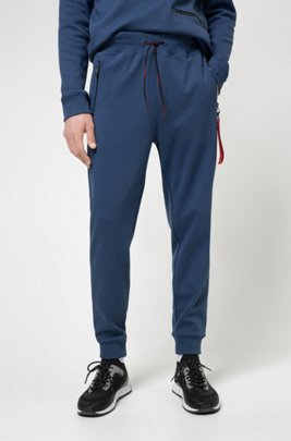 Interlock-cotton tracksuit bottoms with reverse-logo patch, Dark Blue