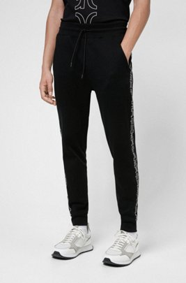 Organic-cotton tracksuit bottoms with cropped logos, Black