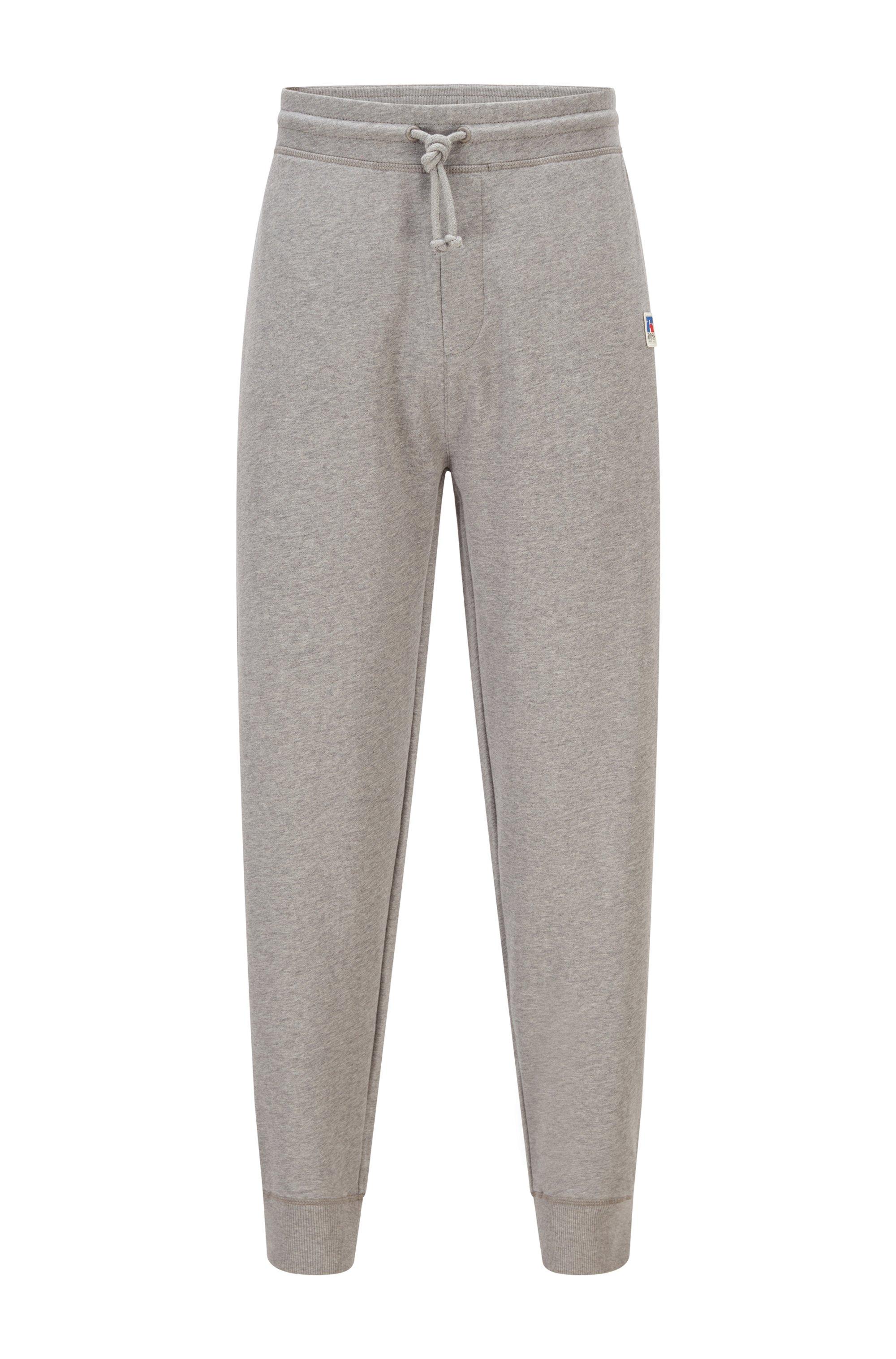 Pantalones de chándal elaborados en algodón orgánico con un logo exclusivo y puños en los bajos, Gris