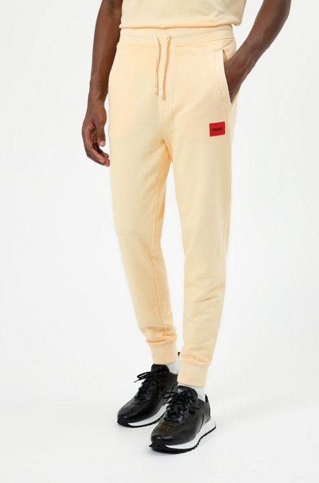 Tracksuit bottoms in terry cotton with red logo label, Orange