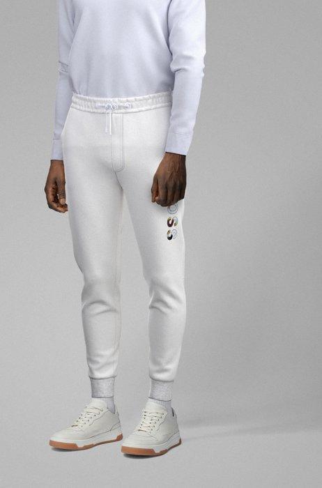 Cotton-blend tracksuit bottoms with graphic logo print by Maxim Zhestkov, White