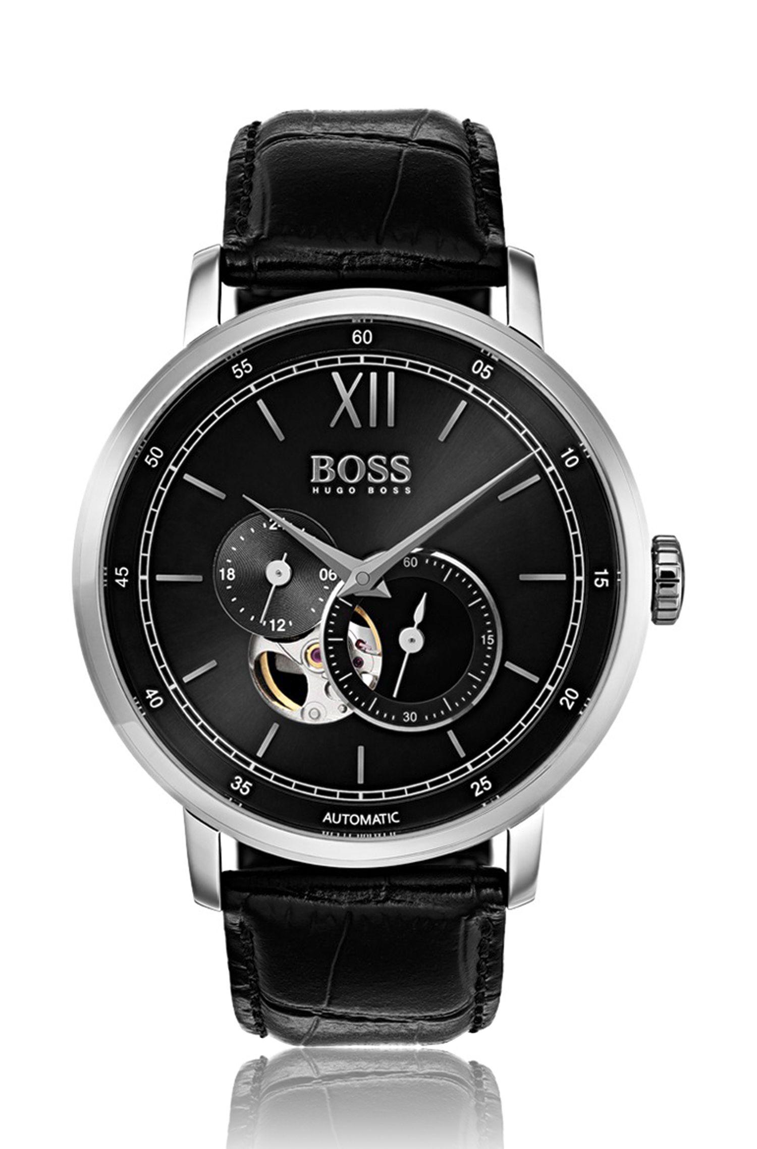 Horloge met meerdere wijzerplaten, zichtbare mechaniek en een polsband met reliëf