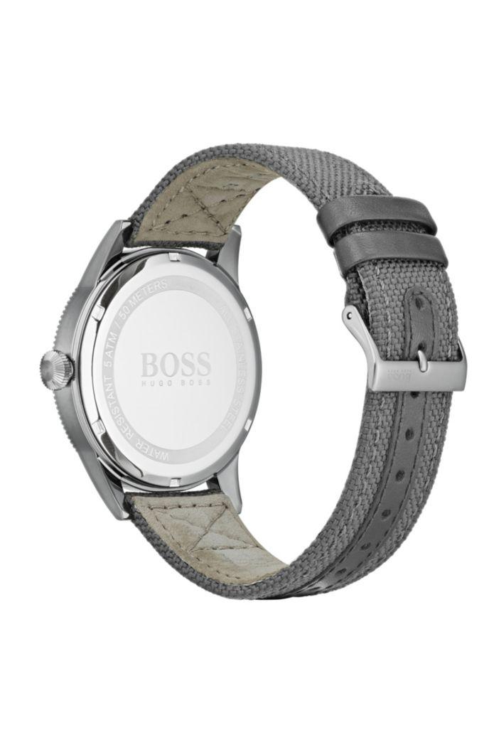 Horloge met getextureerde lunette en een geweven polsband met leren voering
