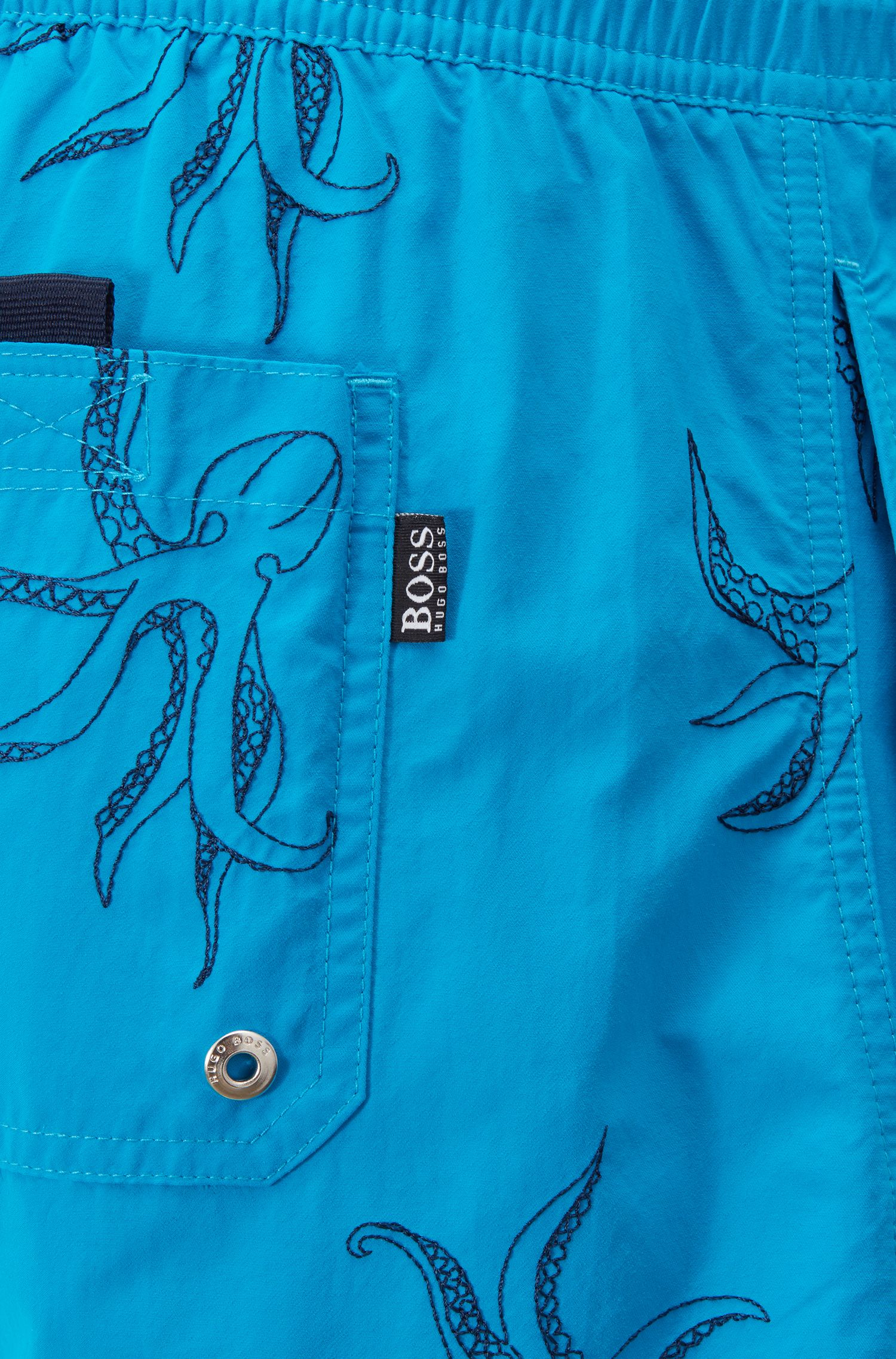 Quick-drying swim shorts with embroidered motif, Turquoise