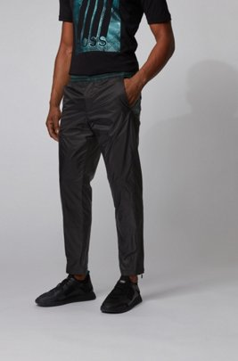 Tapered-fit pants with printed inserts and zipped hems, Black